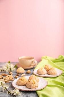 Mandelkekse und eine tasse kaffee auf einer grauen und rosa oberfläche und grünem leinentextil