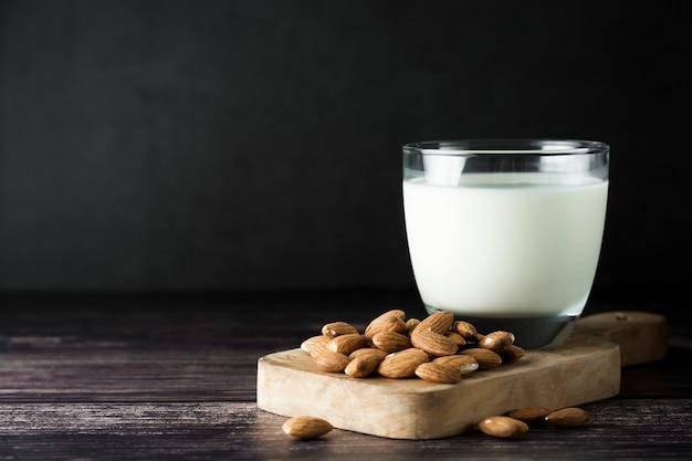 Mandelmilch - alternative zu klassischer milch. ein glas mit mandelmilch und mandelnüssen. dunkles lebensmittelfoto mit copyspace. gesunde, vegane milch.
