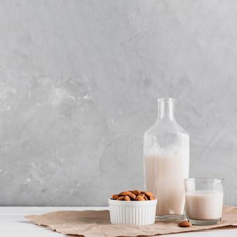 Mandelmilch im glas und in der flasche mit mandeln
