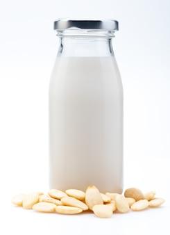 Mandelmilch in der glasflasche. enthält geschälte mandeln. isoliert