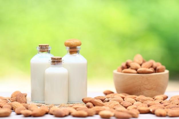Mandelmilch in der glasflasche mit mandeln in einer schüssel verwischte auf dem tisch natur