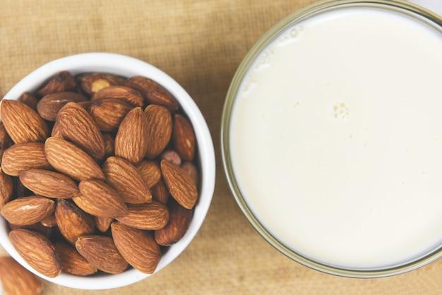 Mandelmilch in schüssel und mandelnüsse auf sackuntergrund /