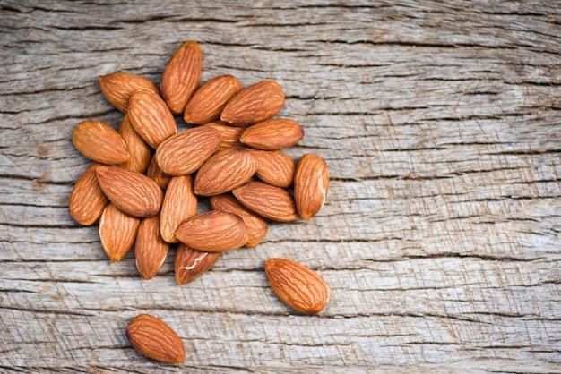 Mandeln auf draufsicht des rustikalen hölzernen hintergrundes - nah herauf natürliches proteinlebensmittel der mandelnüsse und für snack