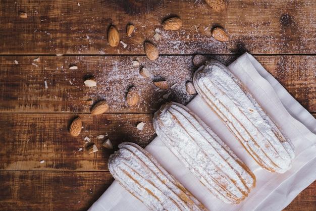 Mandeln mit eclairs auf serviette über dem hölzernen schreibtisch