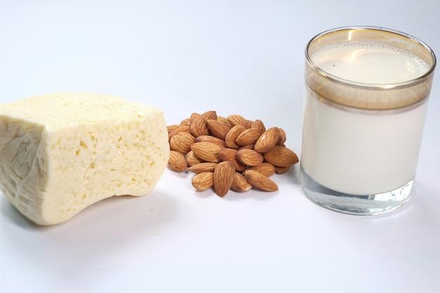 Mandelnuss, käse und milch auf weißer oberfläche.