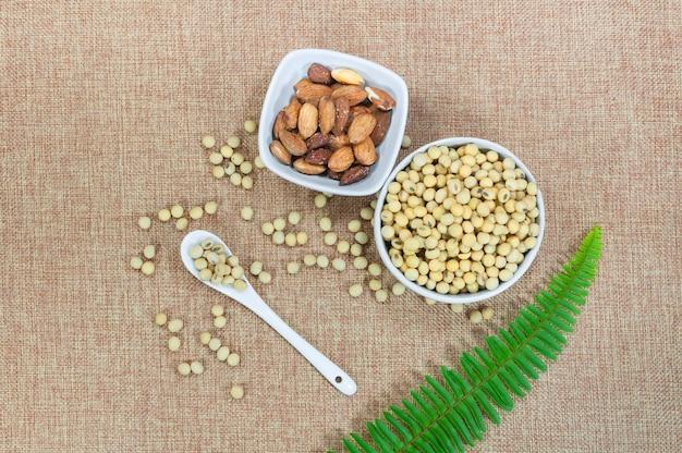 Mandelnuss und sojabohne in weißer schüssel und löffel mit grüner pflanze auf braunem stoff