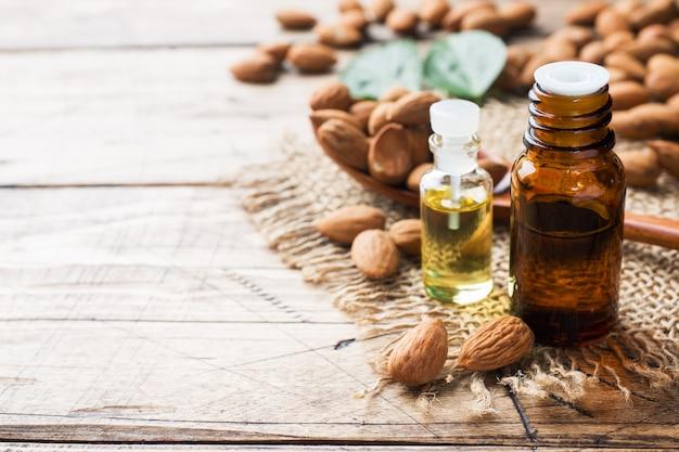 Mandelöl in der flasche auf hölzernem hintergrund. concept spa, aromatherapie und medizin.
