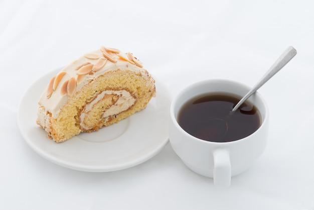 Mandelrollenkuchen auf weißem teller mit heißem getränk