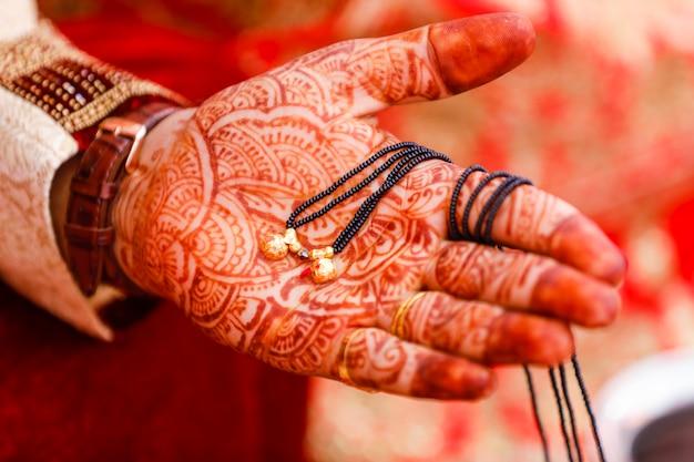 Mangasutra, das in der bräutigamhand hält
