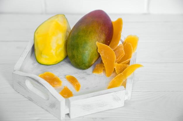 Mango auf weißem holzhintergrund mit saft und getrockneter mango auf weißem holztablett, das konzept gesunder lebensmittel und exotischer früchte
