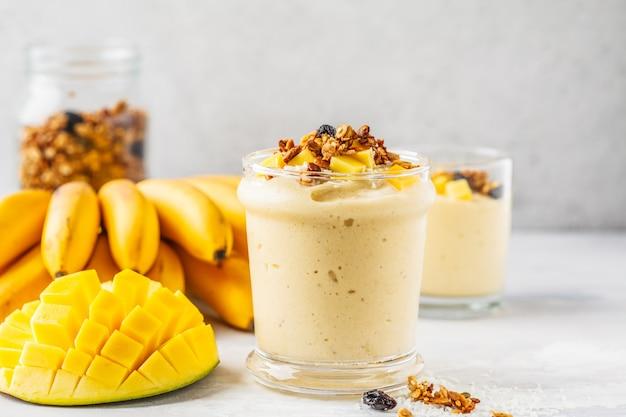 Mango-bananen-smoothie mit müsli und kokosnuss im glas. pflanzliches lebensmittelkonzept.