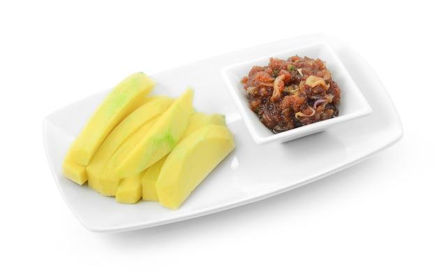 Mango in scheiben geschnitten mit süßer fischsauce auf weiß.
