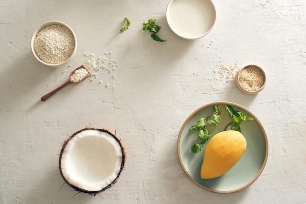 Mango-klebreis mit reis, kokosmilch und zucker, sesam- und mangohintergrund