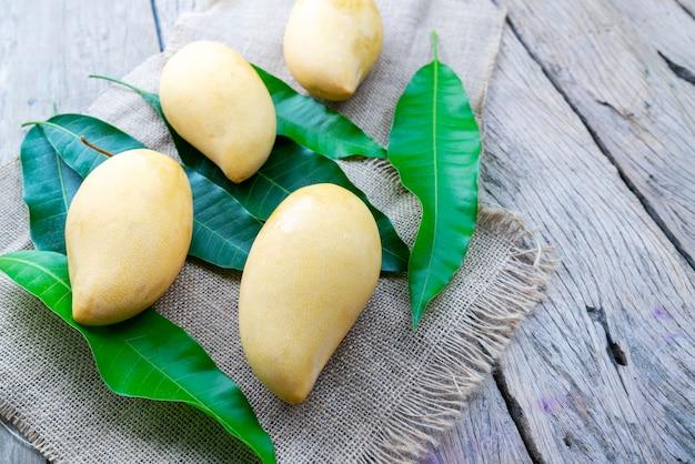 Mango mit blättern auf holztischhintergrund