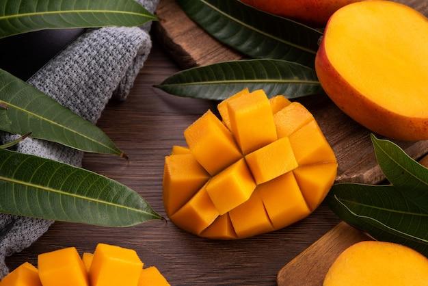Mango. nahaufnahme von frischen reifen mangofrüchten mit blättern über dunklem holztischhintergrund mit grünen blättern.