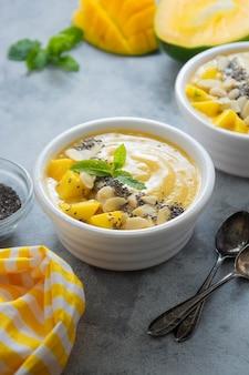 Mango-smoothie-bowl mit chiasamen. leckeres gesundes frühstück.