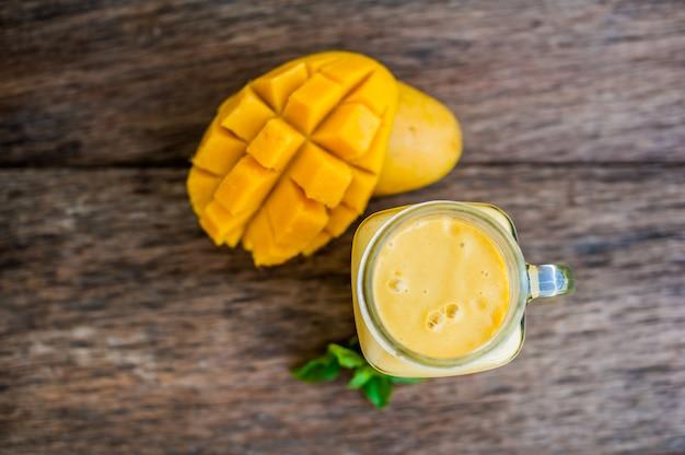 Mango-smoothie in einem einmachglas und mango auf dem alten hölzernen hintergrund. mango-shake.