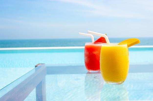 Mango-smoothie und wassermelonen-smoothie mit pool und meer