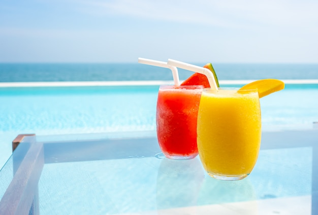 Mango-smoothie und wassermelonen-smoothie mit swimmingpool und meeresstrand