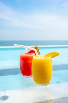 Mango-smoothie und wassermelonen-smoothie mit swimmingpool und meeresstrandhintergrund