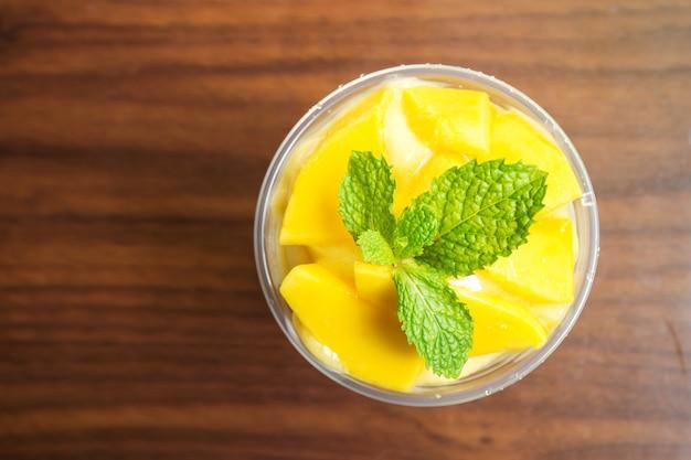 Mango-smoothies in plastikbecher. gesundes getränk der erfrischung. ansicht von oben.