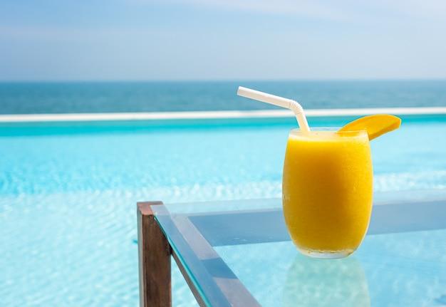 Mango smoothies mit schwimmbad und meer