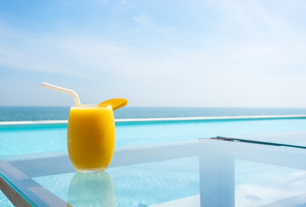 Mango-smoothies mit swimmingpool und meeresstrand