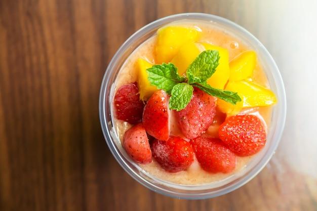 Mango- und erdbeeresmoothies in der plastikschale. gesundes getränk der erfrischung.