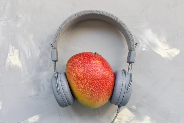 Mango und kopfhörer auf grauem hintergrund