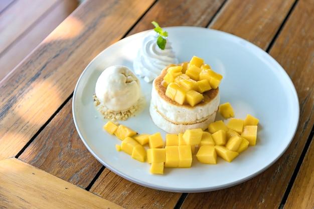Mango- und vanilleeiscreme mit flaumigem kuchen in der weißen platte auf dem holztisch.
