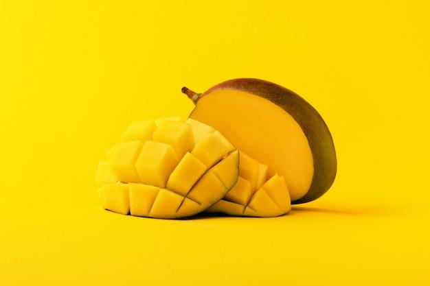 Mangofrucht mit geschnittenen mangowürfeln auf gelbem hintergrund