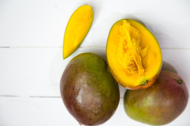 Mangofrucht-nahaufnahme auf weißem hölzernem hintergrund, konzept der tropischen frischen frucht