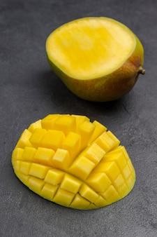 Mangofrucht und gewürfelte mangostücke. gesunde ernährung. draufsicht. schwarze oberfläche