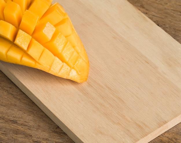 Mangogelb auf hölzernem hintergrund geschnitten. thailändisches lebensmittelkonzept.