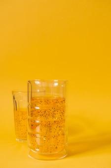 Mangogetränk mit basilikumsamen auf gelbem grund. erfrischungsgetränk mit eis.