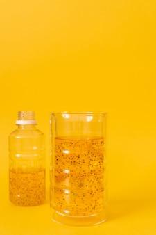 Mangogetränk mit basilikumsamen mit eis auf gelbem grund.
