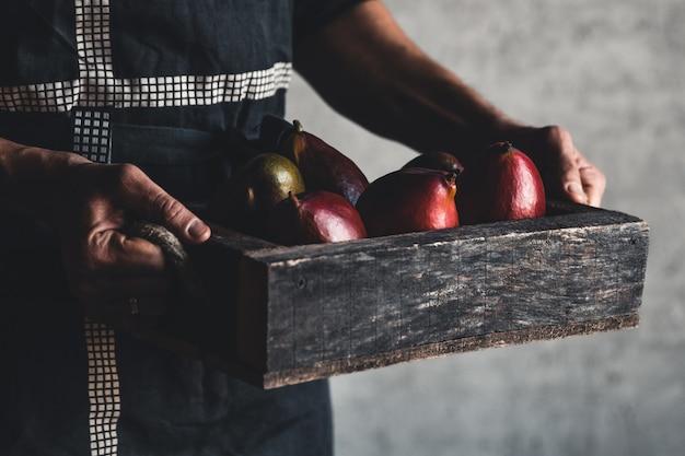Mangohaufen im holzkorb, der von einem obstgartenbauern trägt