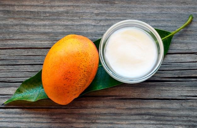 Mangokörperbutter in einer glasschüssel und in einer frischen reifen organischen mangofrucht auf altem holz