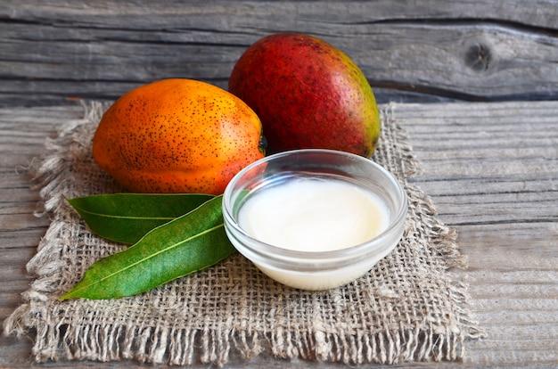 Mangokörperbutter in einer glasschüssel und in frischen reifen organischen mangofrüchten auf altem holz