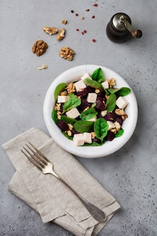 Mangold-, rucola-, rote-bete-, ricotta-käse- und walnusssalat mit olivenöl in einer alten keramikplatte auf einer grauen stein- oder betonoberfläche. selektiver fokus. draufsicht. speicherplatz kopieren.