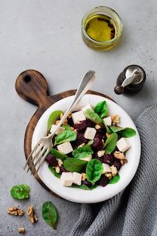 Mangold-, rucola-, rote-bete-, ricotta-käse- und walnusssalat mit olivenöl in einer alten keramikplatte auf einer grauen stein- oder betonoberfläche. selektiver fokus. draufsicht.