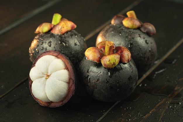 Mangostan und querschnitt zeigen die dicke lila haut und das weiße fleisch