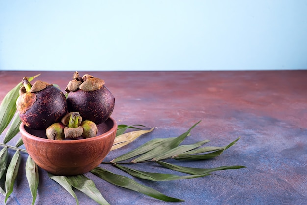 Mangostanfrucht der königin der früchte auf einer schüssel mit palmblatt auf steinhintergrund mit kopienraum
