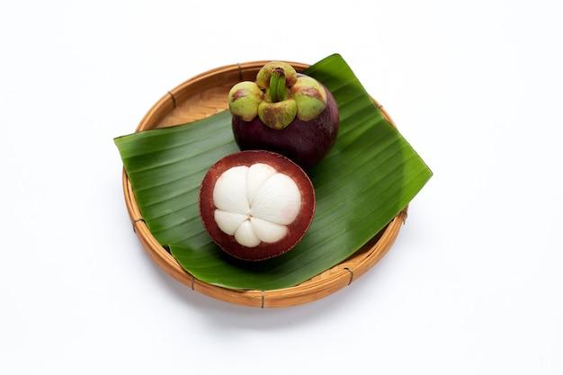 Mangostanfrucht im bambuskorb auf weißem hintergrund.