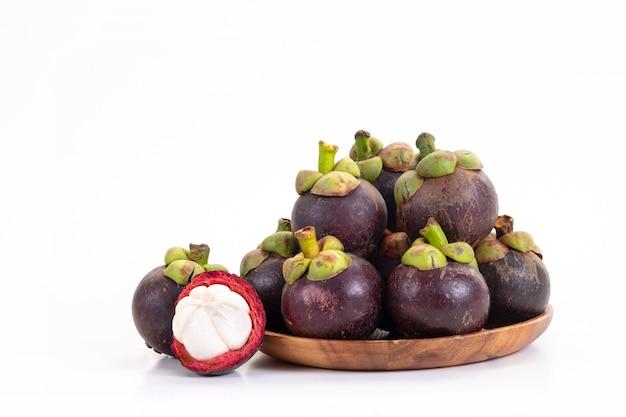 Mangostanfrucht und querschnitt, der die starke purpurrote haut und das weiß auf weiß zeigt