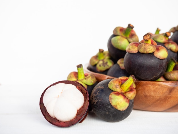 Mangostanfrüchte (garcinia mangostana) in der hölzernen platte und in der schale halb auf weißem hintergrund.