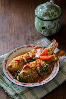 Mangut nila ist traditionelles essen aus indonesien. hergestellt aus gebratenem fisch gemischt mit scharfer kokos-currysauce