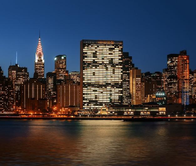 Manhattan bei nacht. skyline von new york city mit lichtern und reflexionen.