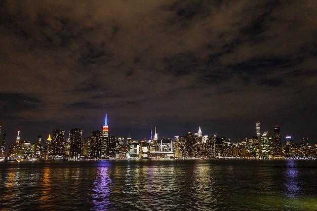 Manhattan in der nacht aus der ferne mit flussreflexion erschossen