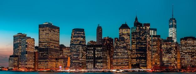 Manhattan in der nacht mit lichtern und reflexionen. skyline von new york city